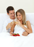 Happy couple drinking Champagne with strawberries Stock Photos