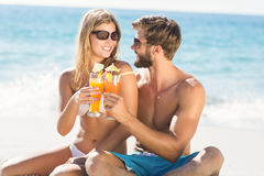 Happy couple drinking a cocktail. At the beach royalty free stock images