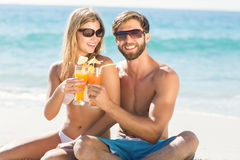 Happy couple drinking a cocktail. At the beach stock images