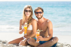 Happy couple drinking a cocktail. At the beach royalty free stock photography