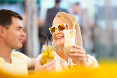 Happy couple drinking cocktails outdoor Royalty Free Stock Images
