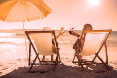 Happy couple drinking cocktails while relaxing on their deck chairs Royalty Free Stock Photography