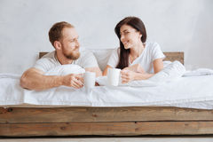 Happy couple drinking coffee in bed. We can get out of bad later. Young couple relaxing at home while lying in bed with a cup of aromatic coffee Royalty Free Stock Photography
