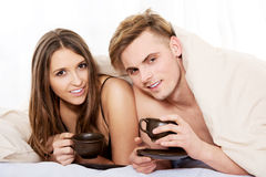 Happy couple drinking coffee in bed. Royalty Free Stock Images