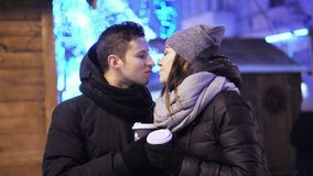 Happy couple drinking coffee on the christmas fair under the snowfall. Merry Christmas and Happy New Year. Happy couple drinking coffee on the christmas fair stock video footage