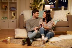 Happy couple drinking coffee and eating at home. Hygge, leisure and people concept - happy couple drinking coffee and eating at home royalty free stock image