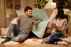 Happy couple drinking coffee and eating at home. Hygge, leisure and people concept - happy couple drinking coffee and eating at home royalty free stock photos