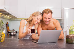 Happy couple drinking coffee and looking at something on computer Royalty Free Stock Image