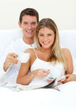 Happy couple drinking coffee lying on their bed Royalty Free Stock Photography