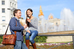 Happy couple drinking coffee talking in Barcelona. Flirting having fun on travel. Happy urban young men and women laughing relaxing on Placa de Catalunya stock photos