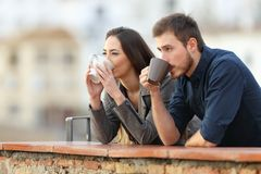 Couple drinking coffee watching views in a balcony. Happy couple drinking coffee watching views in a terrace royalty free stock images