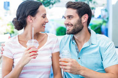 Happy couple drinking milkshakes together. In a cafe stock photo