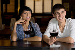 Happy couple drinking red wine at the bar royalty free stock photography