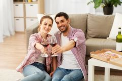 Happy couple drinking red wine at home stock image