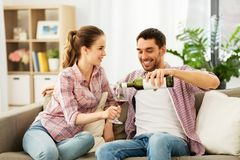 Happy couple drinking red wine at home stock photography