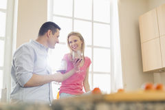 Happy couple drinking red wine in kitchen Stock Photography