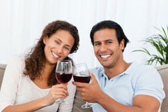 Happy couple drinking red wine sitting on the sofa Royalty Free Stock Images