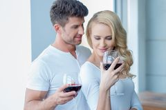 Happy couple drinking red wine to celebrate Stock Photography