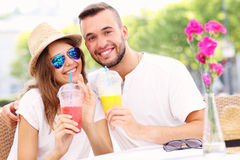 Happy couple drinking smoothies in an outside cafe Stock Image