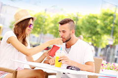 Happy couple drinking smoothies in an outside cafe Stock Photography