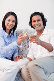 Happy couple drinking sparkling wine on the sofa Royalty Free Stock Photos