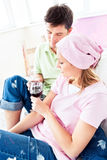 Happy couple drinking wine after painting a room Royalty Free Stock Images