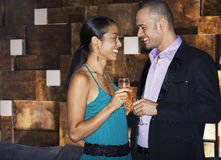 Happy Couple With Drinks In Bar. Side view of a smiling couple standing face to face with drinks in bar Royalty Free Stock Photos