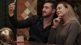 Happy couple with drinks in the bar taking funny selfie via smartphone stock video