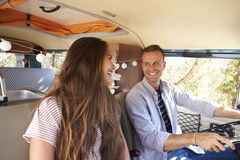 Happy couple driving a camper van looking at each other Royalty Free Stock Images