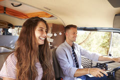 Happy couple driving a camper van on a road trip vacation Stock Photo