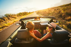 Happy Couple Driving in Convertible. Happy Young Couple Driving Along Country Road in Convertible at Sunset Royalty Free Stock Photos