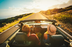Happy Couple Driving in Convertible. Happy Young Couple Driving Along Country Road in Convertible at Sunset Stock Photography