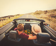 Happy Couple Driving in Convertible. Happy Young Couple Driving Along Country Road in Convertible at Sunset Royalty Free Stock Image