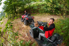 Happy couple driving four-wheelers ATV Royalty Free Stock Images