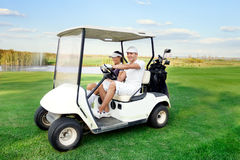 Happy couple driving a golf-cart Royalty Free Stock Images