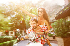 Happy couple driving scooter Royalty Free Stock Images