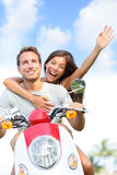 Happy couple driving scooter having fun in summer Stock Images