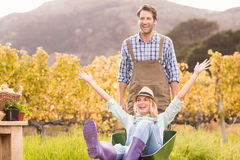 Happy couple in dungarees pushing a wheelbarrow Royalty Free Stock Images