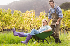 Happy couple in dungarees pushing a wheelbarrow Stock Photography