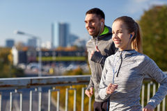Happy couple with earphones running in city. Fitness, sport, people, technology and lifestyle concept - happy couple running and listening to music in earphones Stock Images
