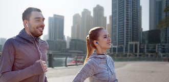 Happy couple with earphones running in city Royalty Free Stock Photo