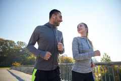 Happy couple with earphones running outdoors Stock Image