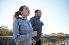 Happy couple with earphones running outdoors Royalty Free Stock Image