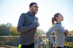 Happy couple with earphones running outdoors Royalty Free Stock Photography