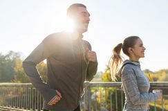 Happy couple with earphones running outdoors Royalty Free Stock Photo