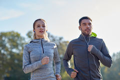 Happy couple with earphones running outdoors Royalty Free Stock Photos