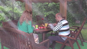 Happy couple eat barbeque food in bower. Romantic family supper stock video footage