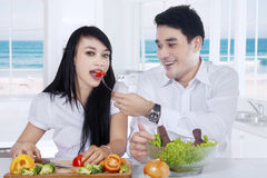 Happy couple eat salad at home Stock Photos