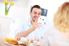 Happy couple eating breakfast and taking pictures Royalty Free Stock Photos