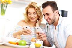 Happy couple eating breakfast and using smart phone Stock Photos